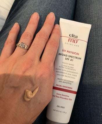 The tan-colored sunscreen on a reviewer's hand