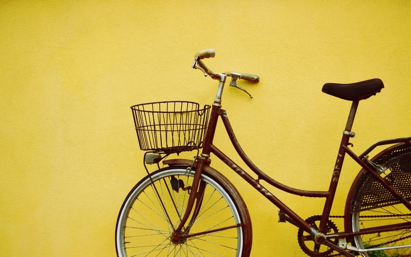 Brown bike with basket with a yellow wall contrasting