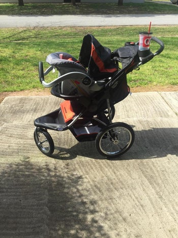 a review photo of the carseat and the jogging stroller outside with a big gulp drink in the cup holder and the stroller is black and orange