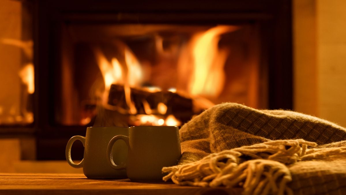 Two mugs and blanket sit in front of a fireplace