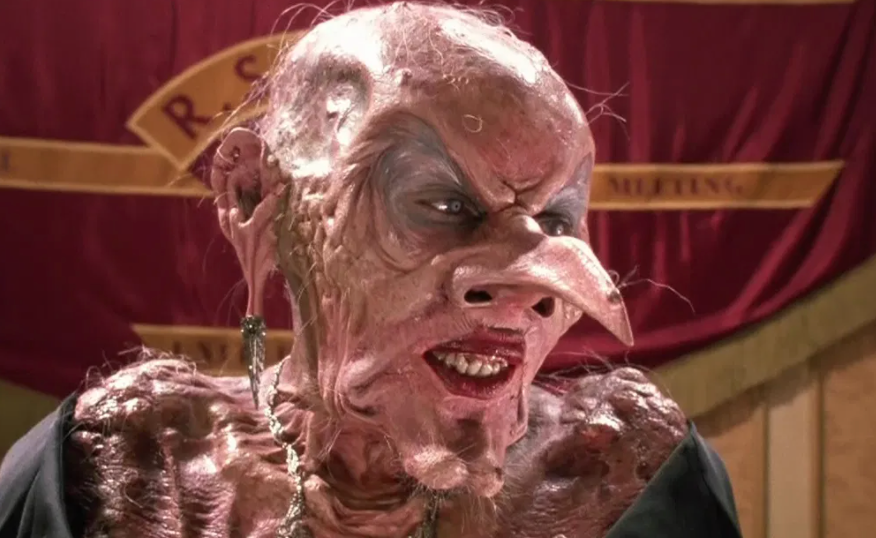 Close-up of a bald witch with lipstick and a pointy nose