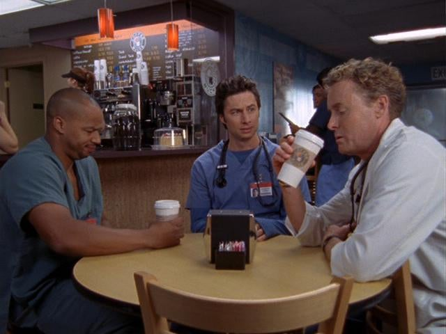 three male nurses sit at a coffee shop drinking out of coffee cups