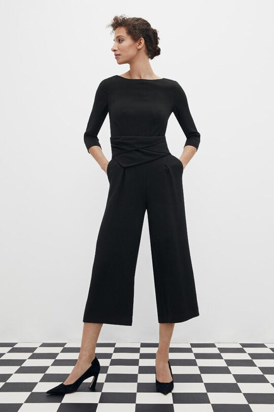 a model in a cropped black jump suit