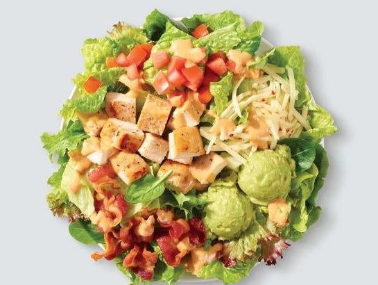 A salad with bacon, grilled chicken, cheese, diced tomatoes, avocado, and southwest ranch dressing