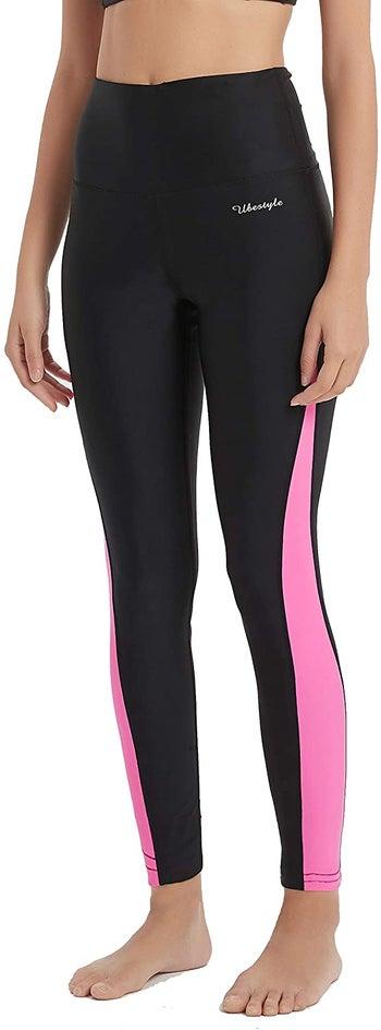 model in black high-waist leggings with pink stripe down sides of leg