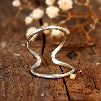 The two loop silver ring resting on a table