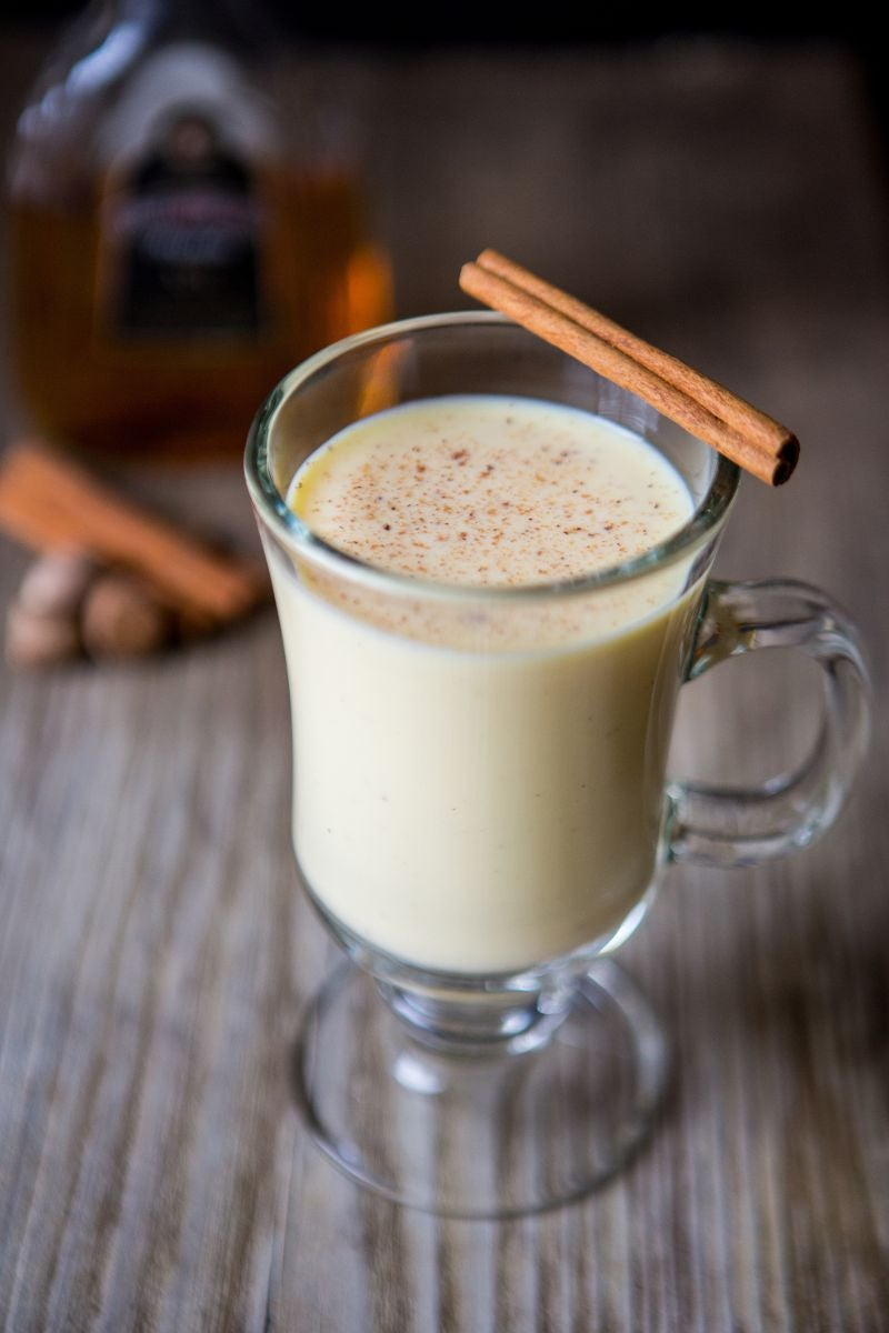 A glass of eggnog with a cinnamon stick