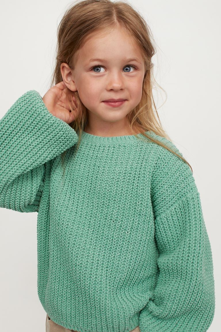 a child in an oversized green sweater with balloon sleeves
