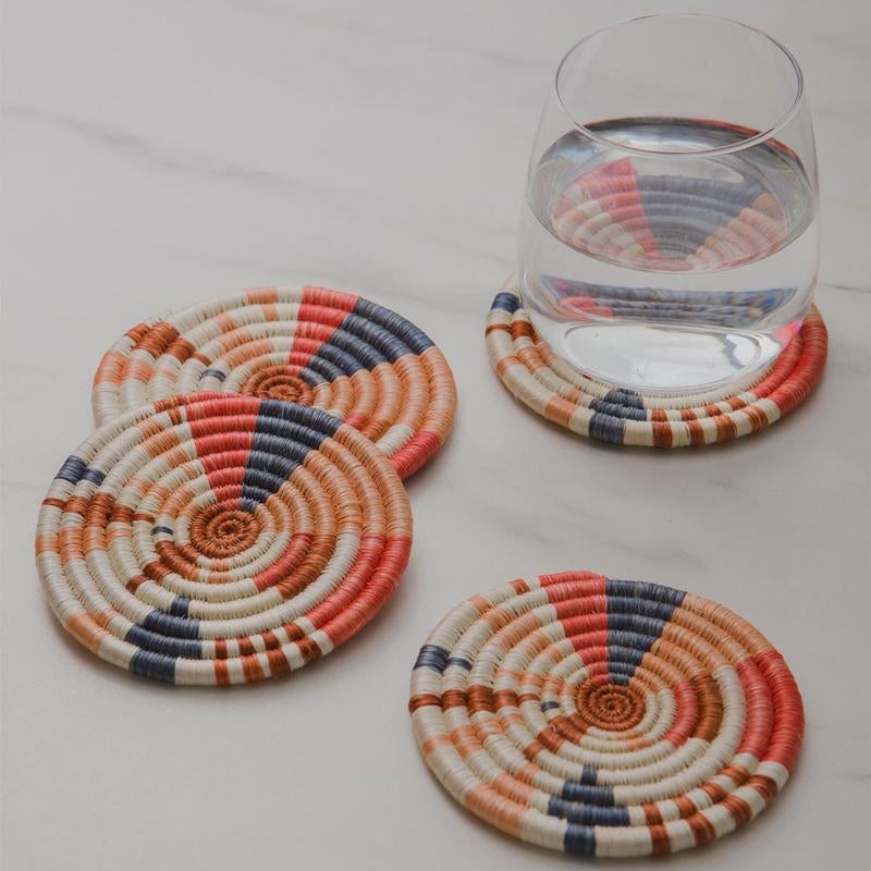Round woven coasters that are red, blue, orange, and salmon