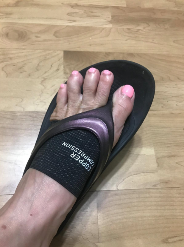 reviewer wearing the band on their foot and a flip-flop