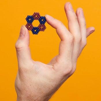 model holding multi-colored Speks
