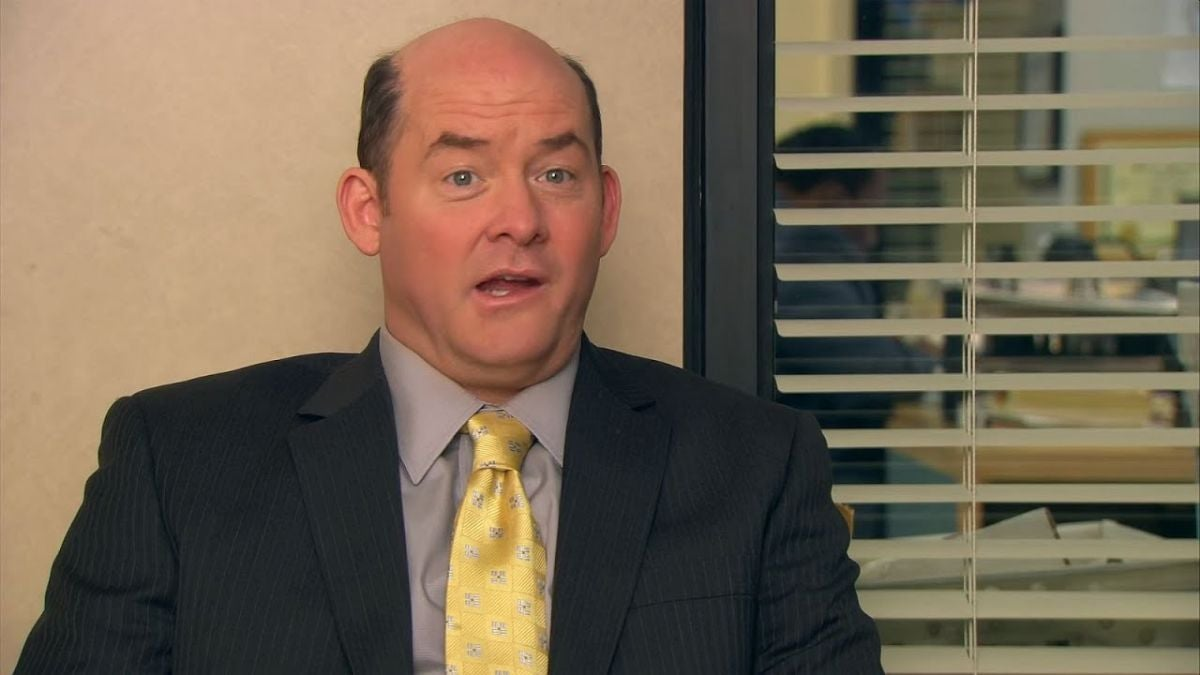 Todd Packer is sitting in the office with his back up against open blinds