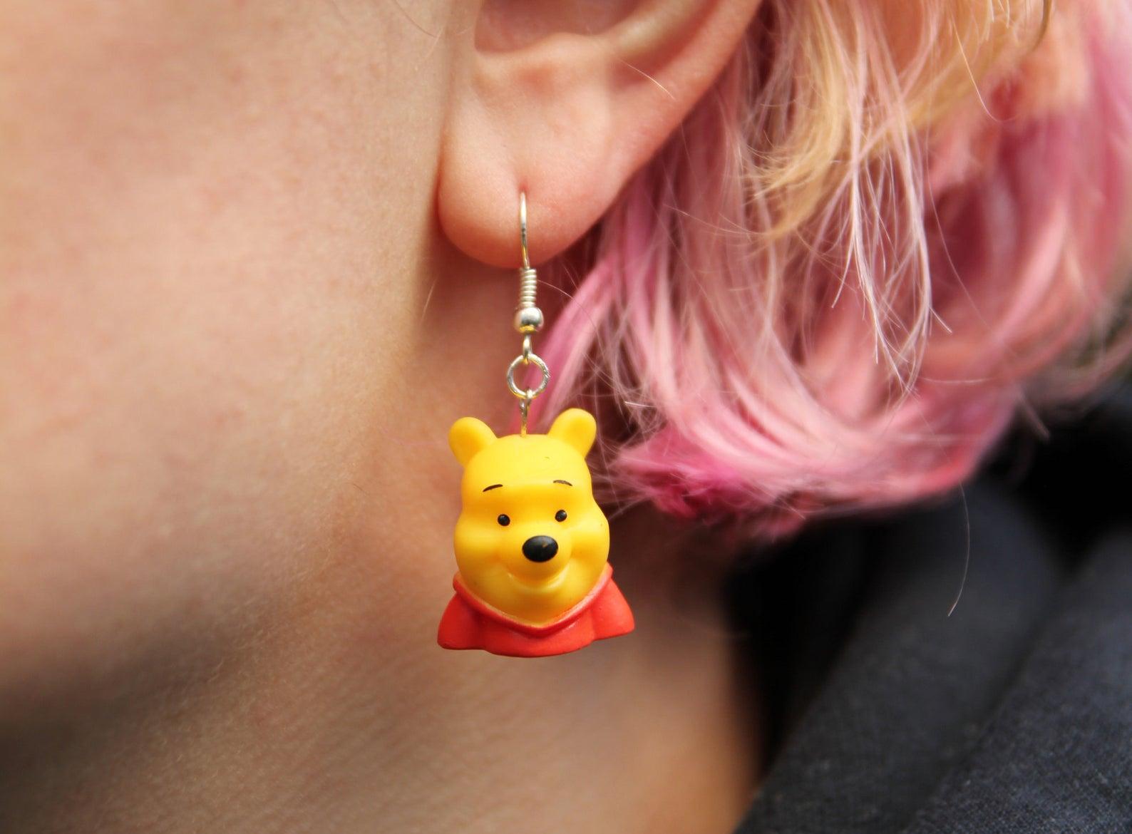 person wearing winnie the pooh earrings