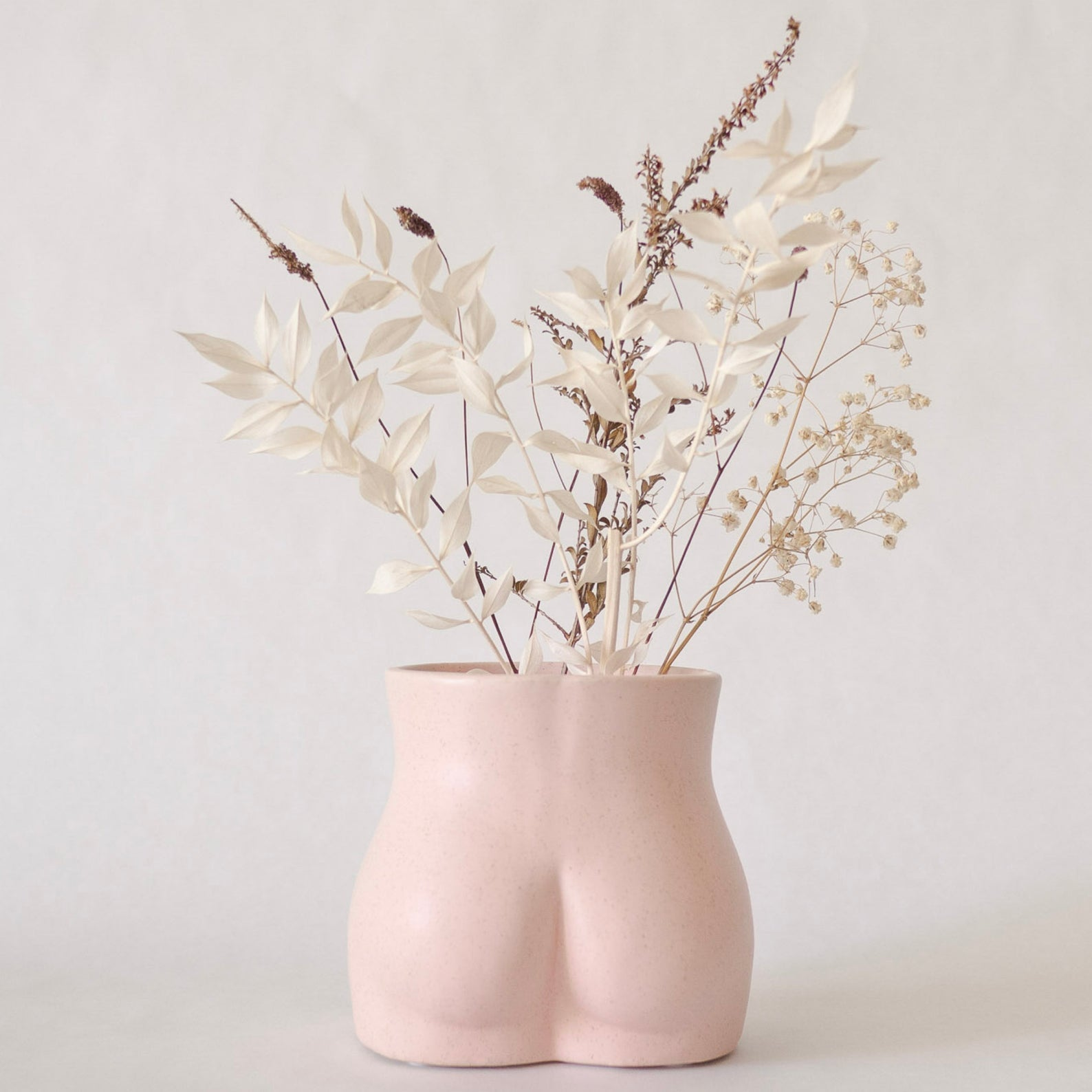 Pink ceramic vase shaped like a butt with flowers in it