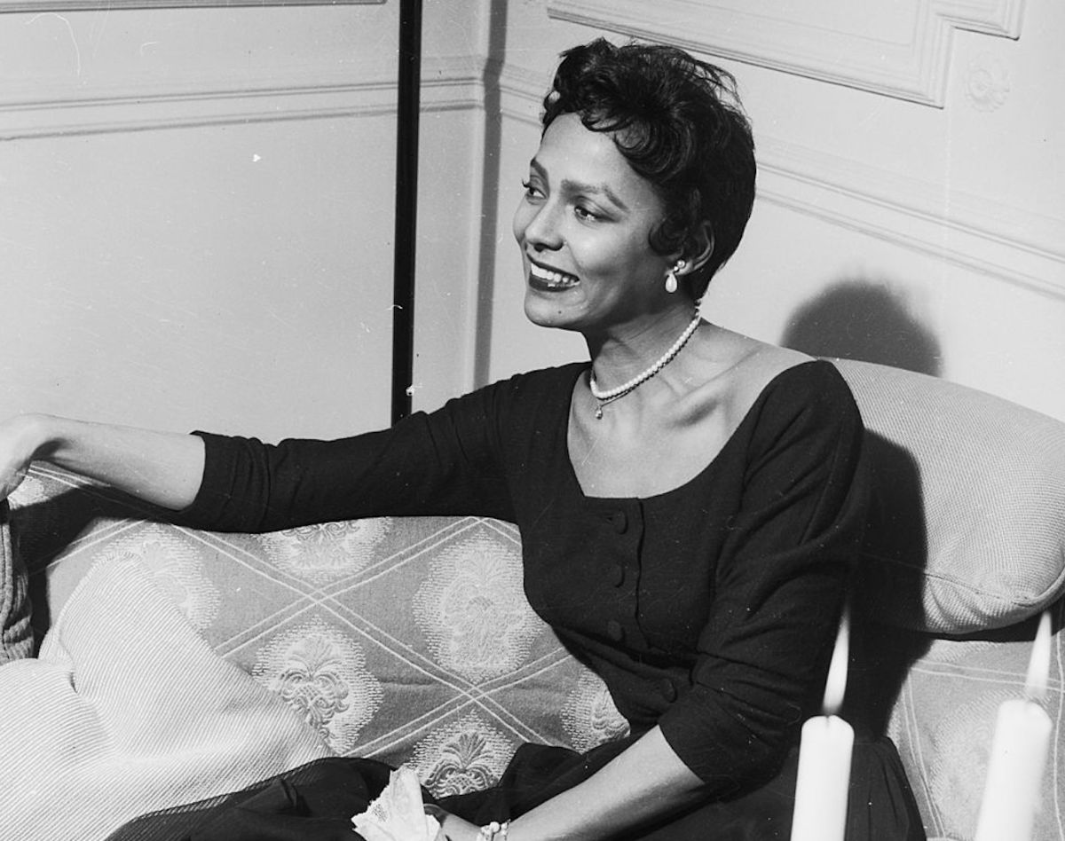 A woman with a pixie haircut is wearing a pearl necklace and is smiling. She wears a long-sleeved dress with buttons down the front and is sitting in a plush chair