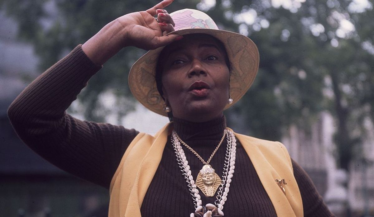A woman is holding the brim of a bucket hat on her head. She also wears a long-sleeved shirt underneath a cotton vest, and sports long necklaces