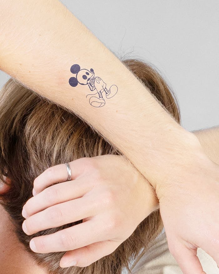a model with an outline of mickey getting an xray as a tattoo
