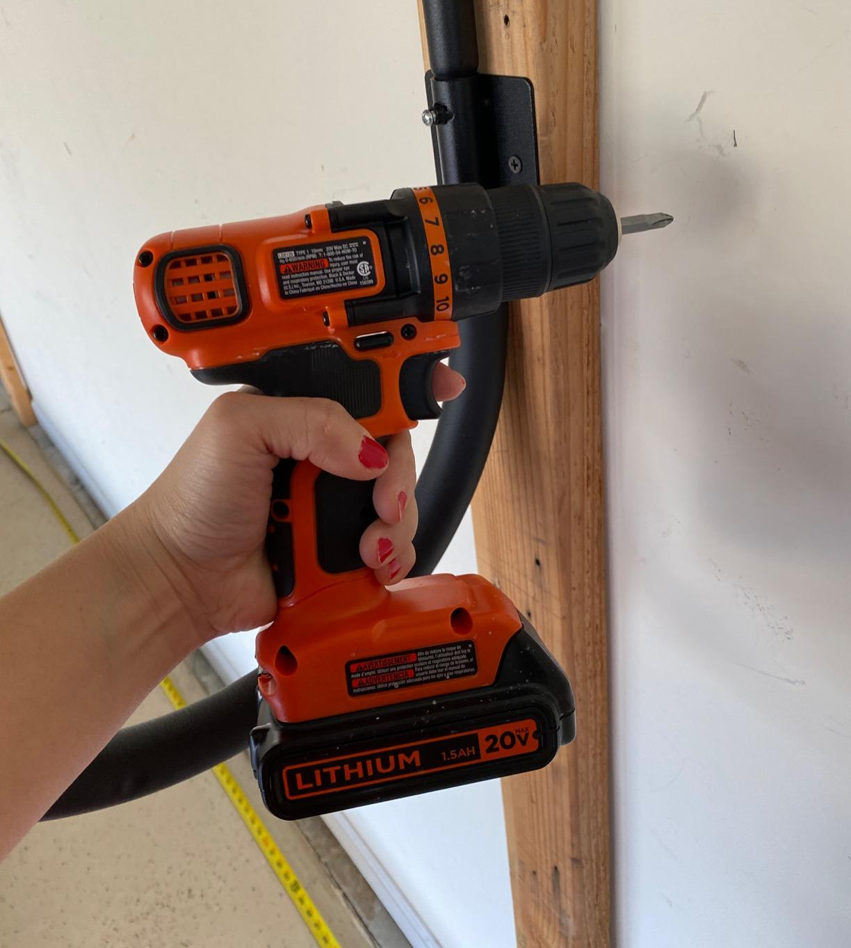 reviewer's hand holding the drill