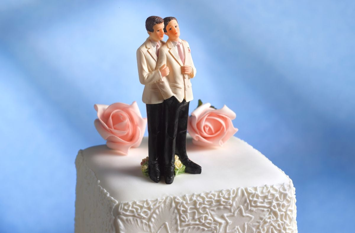 Two groom figurines on top of a wedding cake