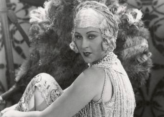 A woman with thin eyebrows wears a large headband with flowers. Her dress is made of pearls