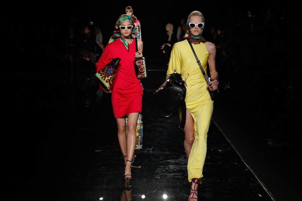 Models on a runway wearing one-shoulder dresses, scarves on their head, and vintage, big sunglasses