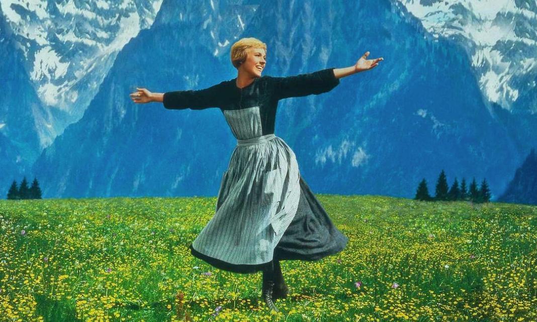 A woman wearing a long dress twirls in a field