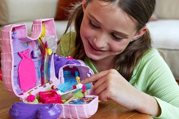 Child model playing with pink and purple plastic unicorn play set