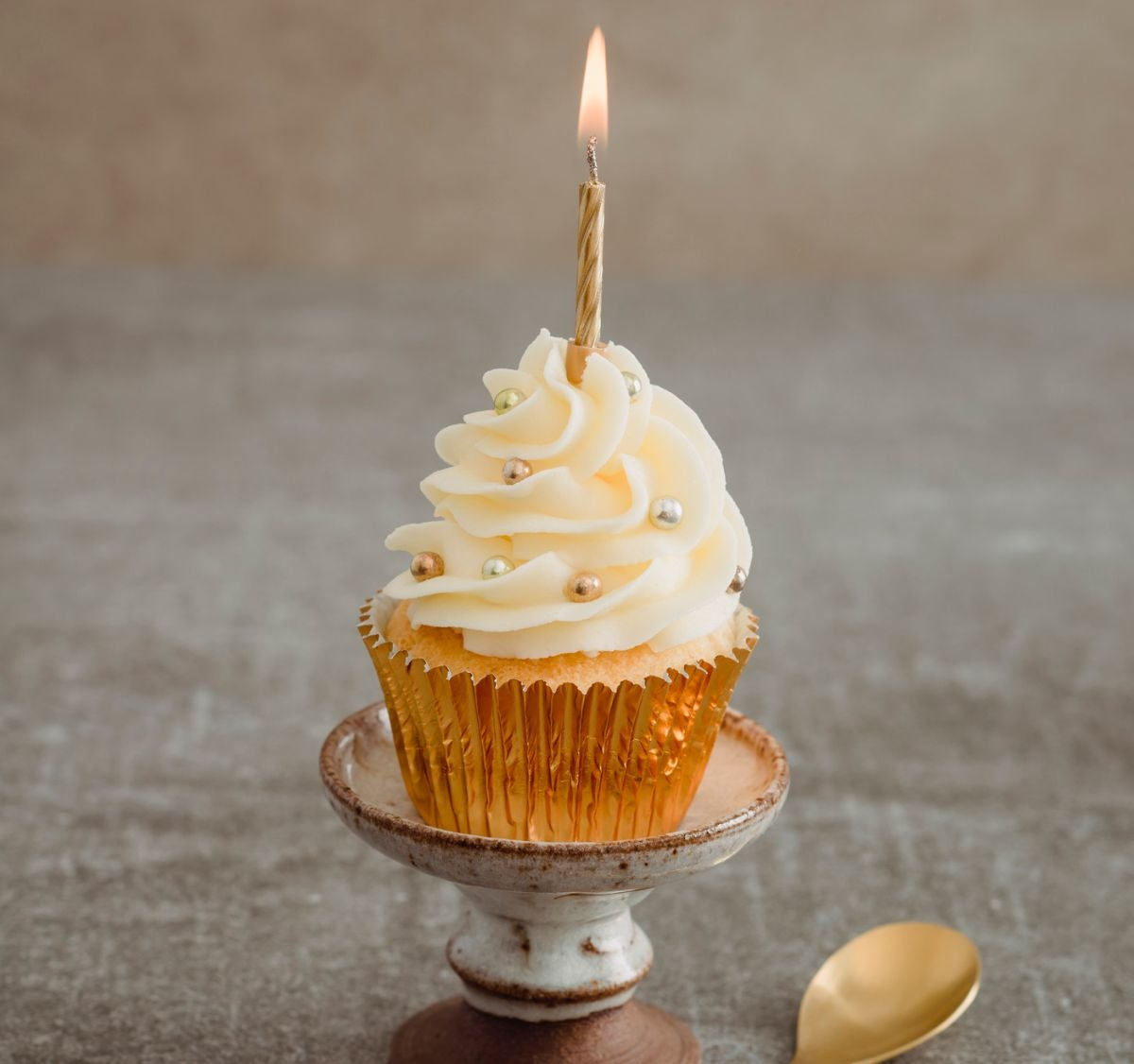 A vanilla cupcake with a sparkler wrapper and sparkly candies on top