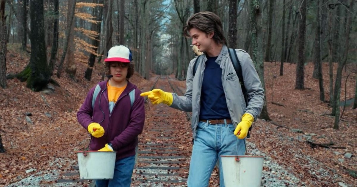 Steve and Dustin are walking in the woods with a bucket in hand and gloves on