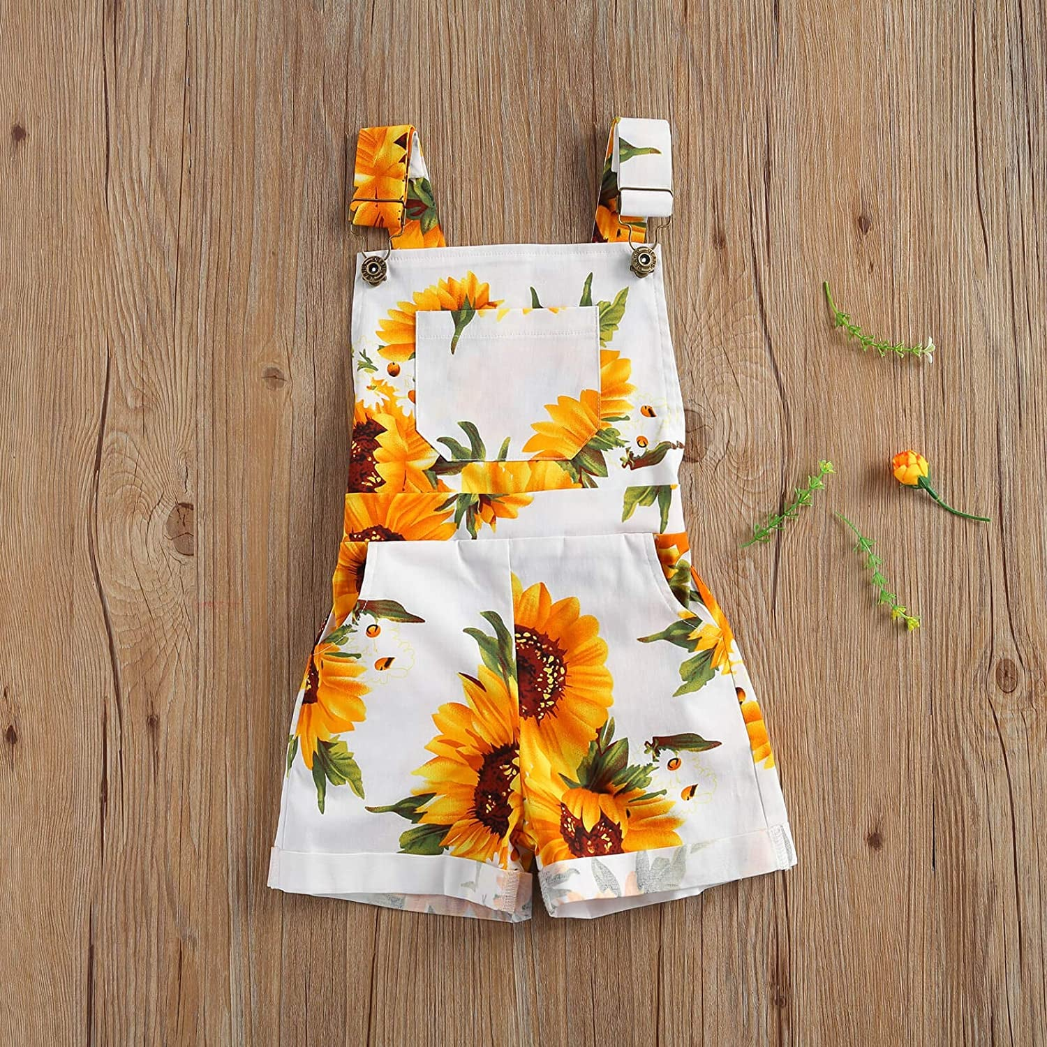 white children's overalls with yellow sunflowers on them