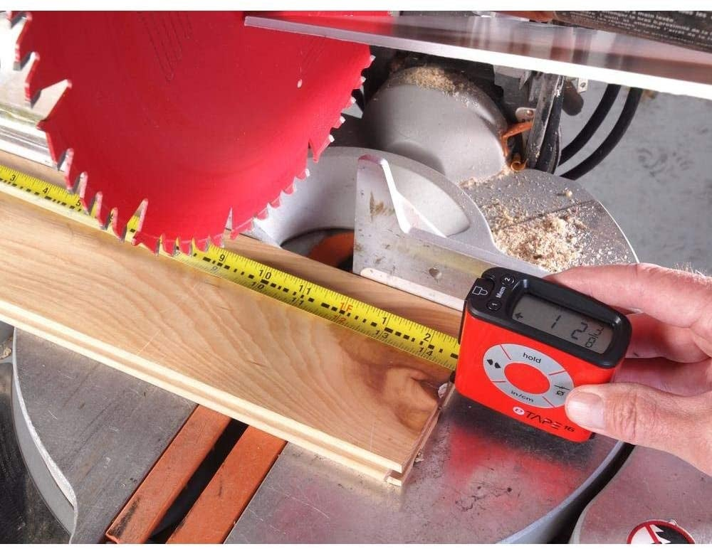 hands using the red digital tape measure to measure a piece of wood