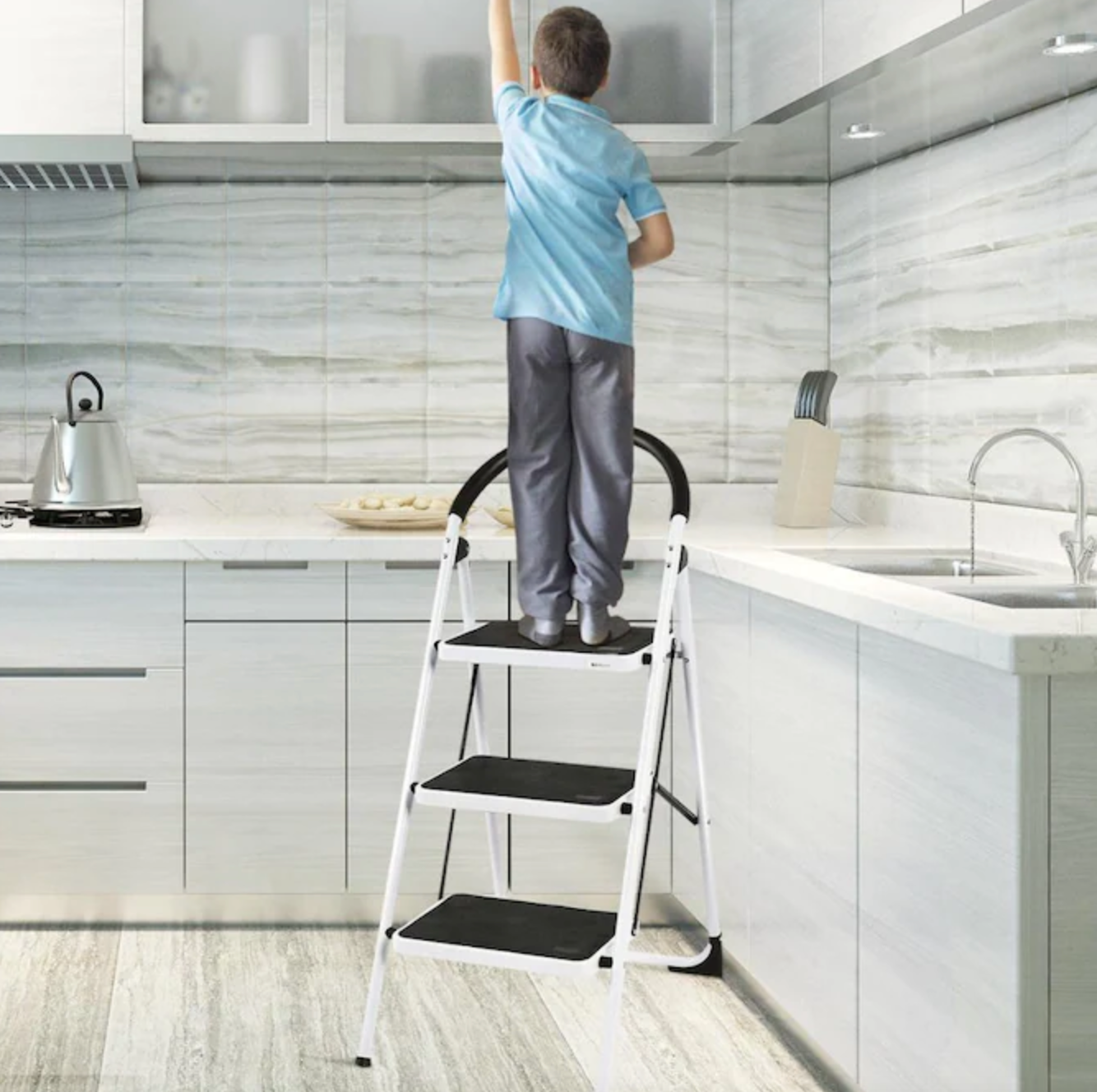 a young person standing on the step ladder in a kitchen