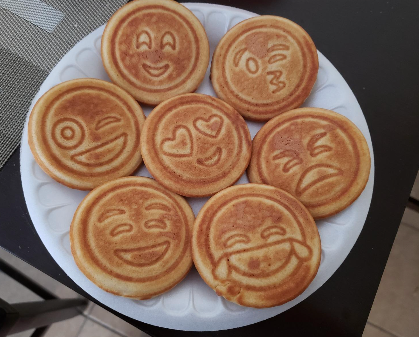 Pancakes in different emoji shapes that are happy, laughing, angry, in love, and mad