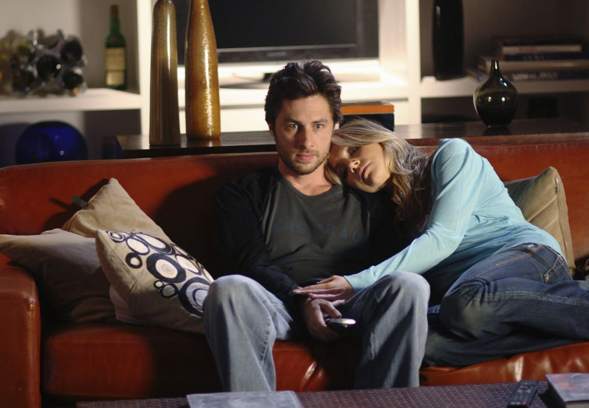 a man and woman sit on a couch, snuggling