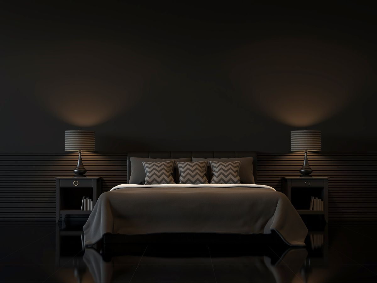 A very dark bedroom with three patterned throw pillows on the bed and two identical nightstands on either side of the bed with identical lamps on top of the nightstands