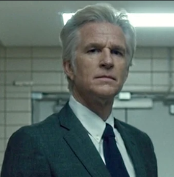 Dr. Brenner is standing in a hallway with a smirk on his face