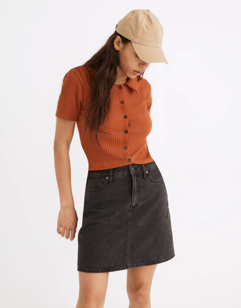 a model in a dark gray denim skirt