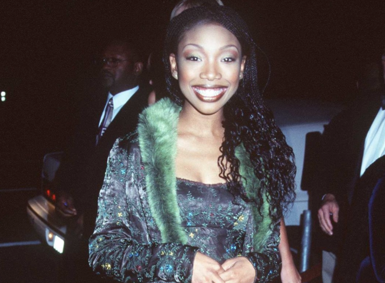 A woman with long braids is wearing a silk dress with a fur coat over it