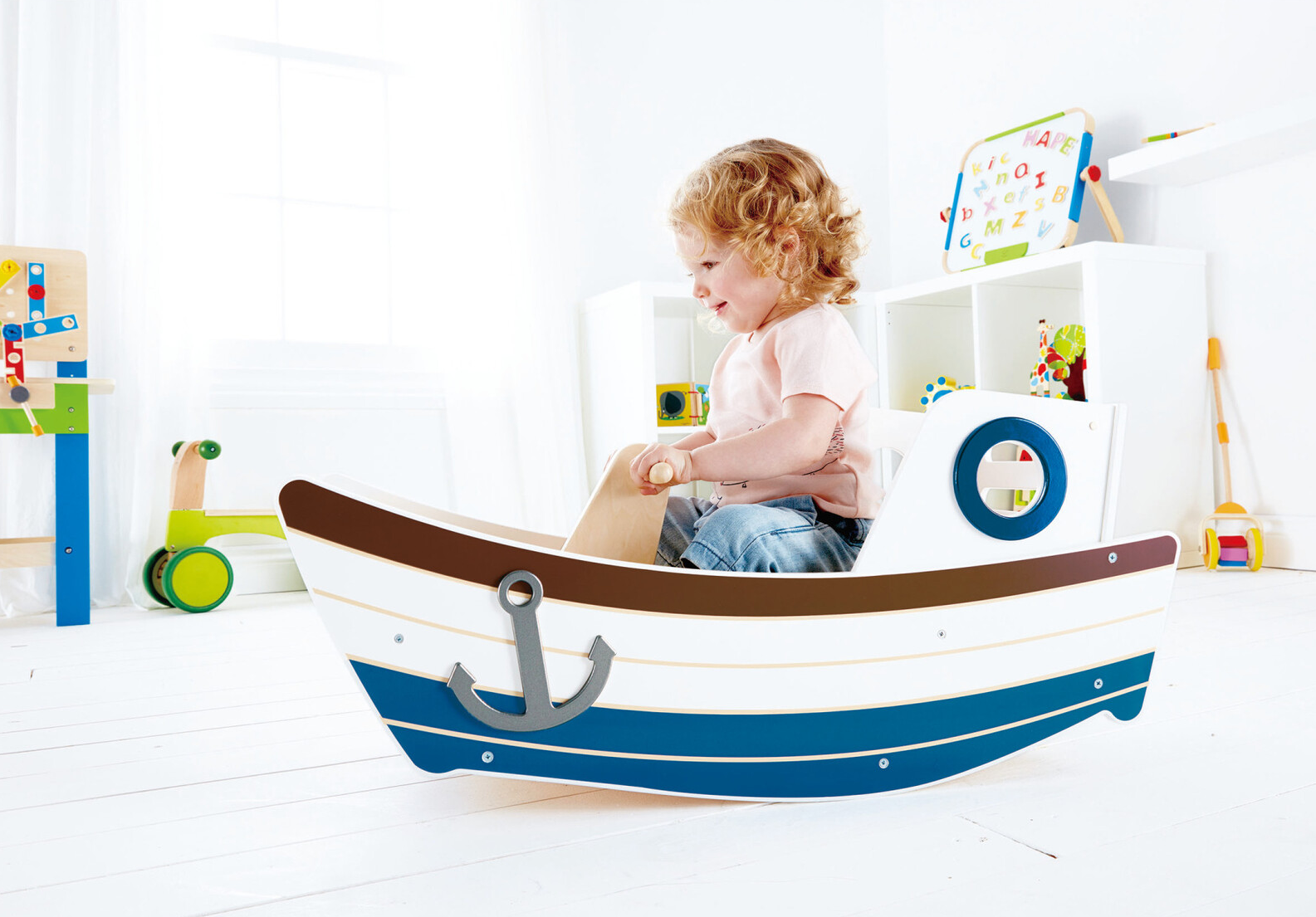 a child in a boat toy that rocks back and forth