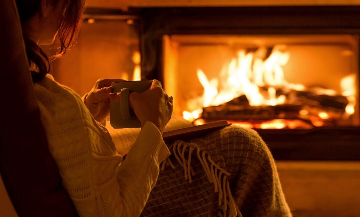A woman sits in a chair with a book on her lap and a mug in her hands as she sits across from a fireplace
