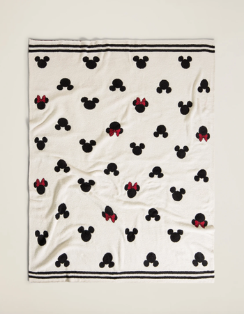 a cream colored blanket with black icons of mickey and minnie heads on them