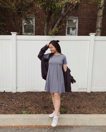 reviewer wearing the gray version with white sneakers and a knitted chunky cardigan