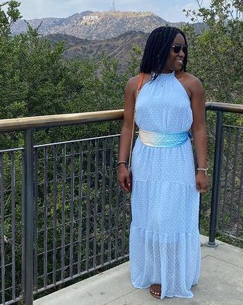 reviewer wearing the light blue dress with a matching waist sash