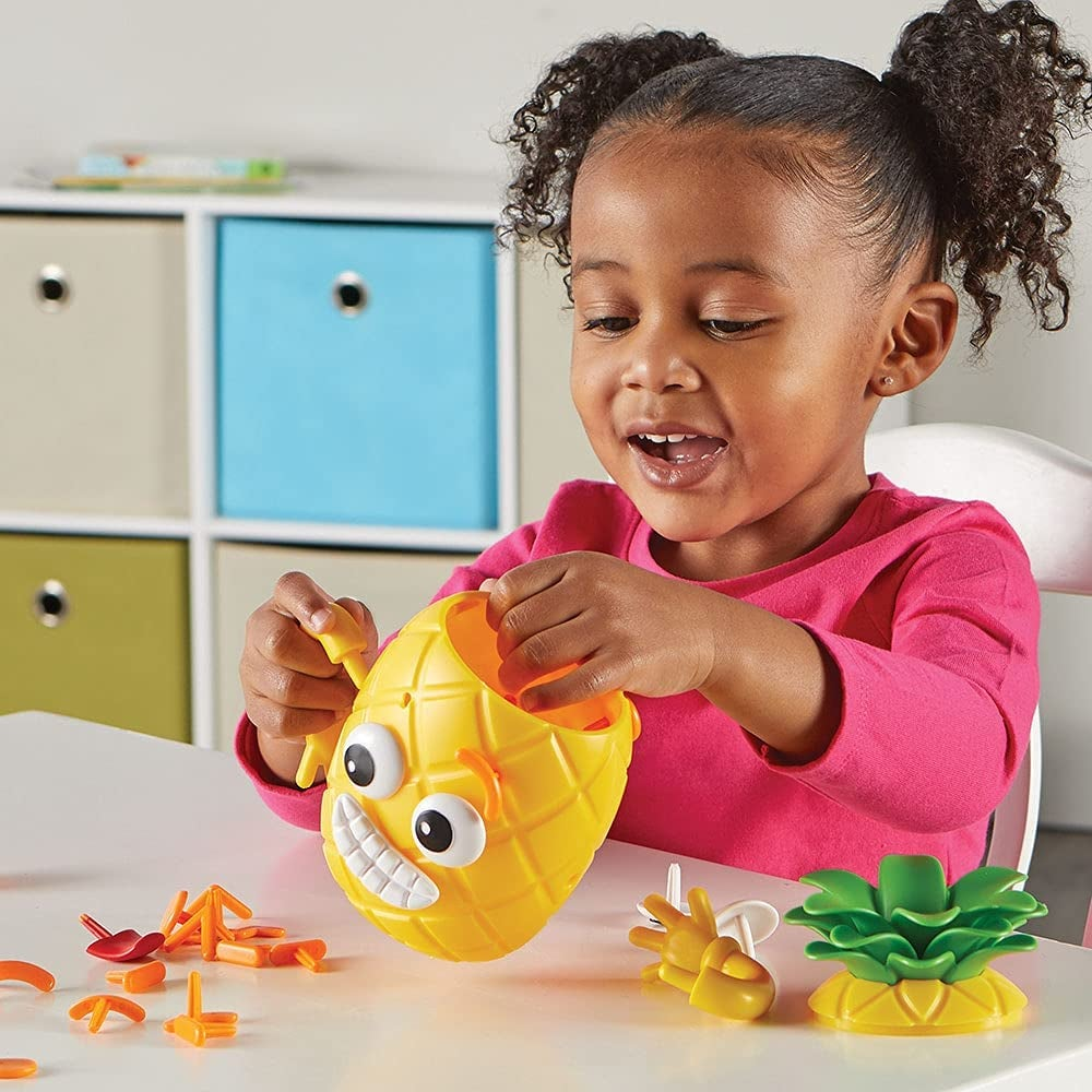 Child model playing with yellow pineapple toy with different faces