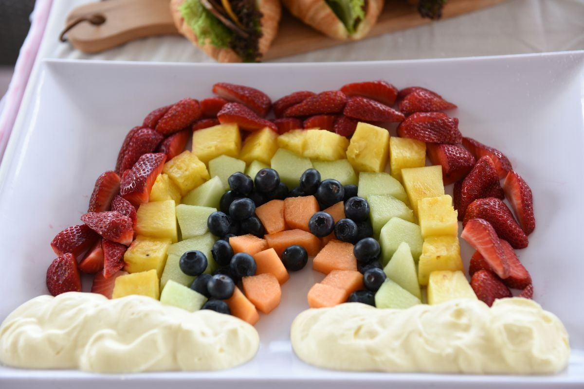 Strawberries, pineapple, honeydew, blueberries, and cantaloupe arranged like a rainbow with yogurt at the ends to resemble clouds