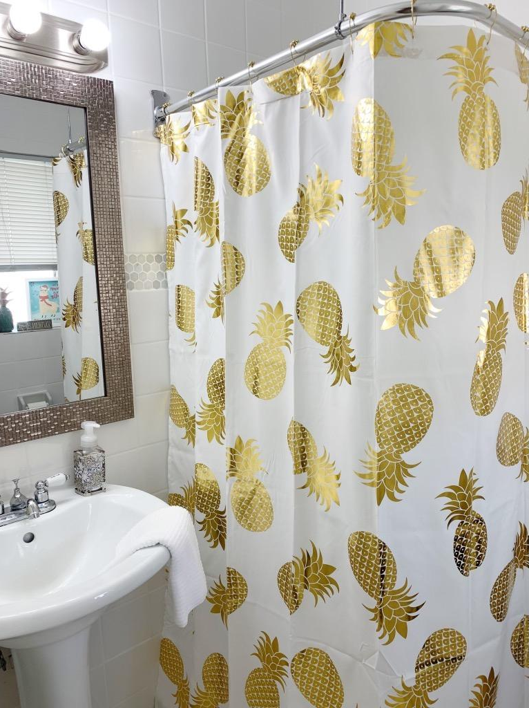 white shower curtain with gold pineapples in a reviewer's home