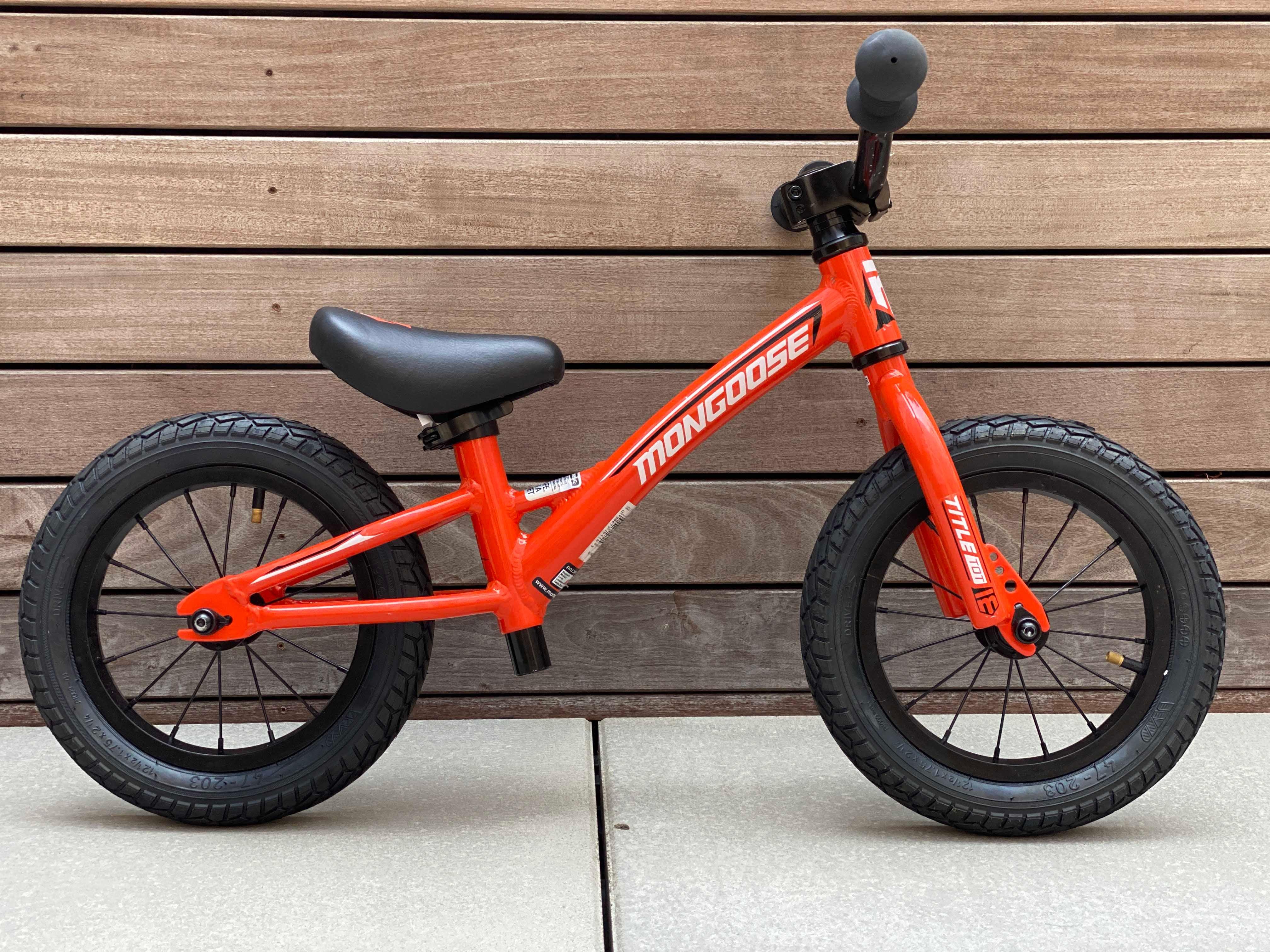 Orange and black balance bike sans pedals