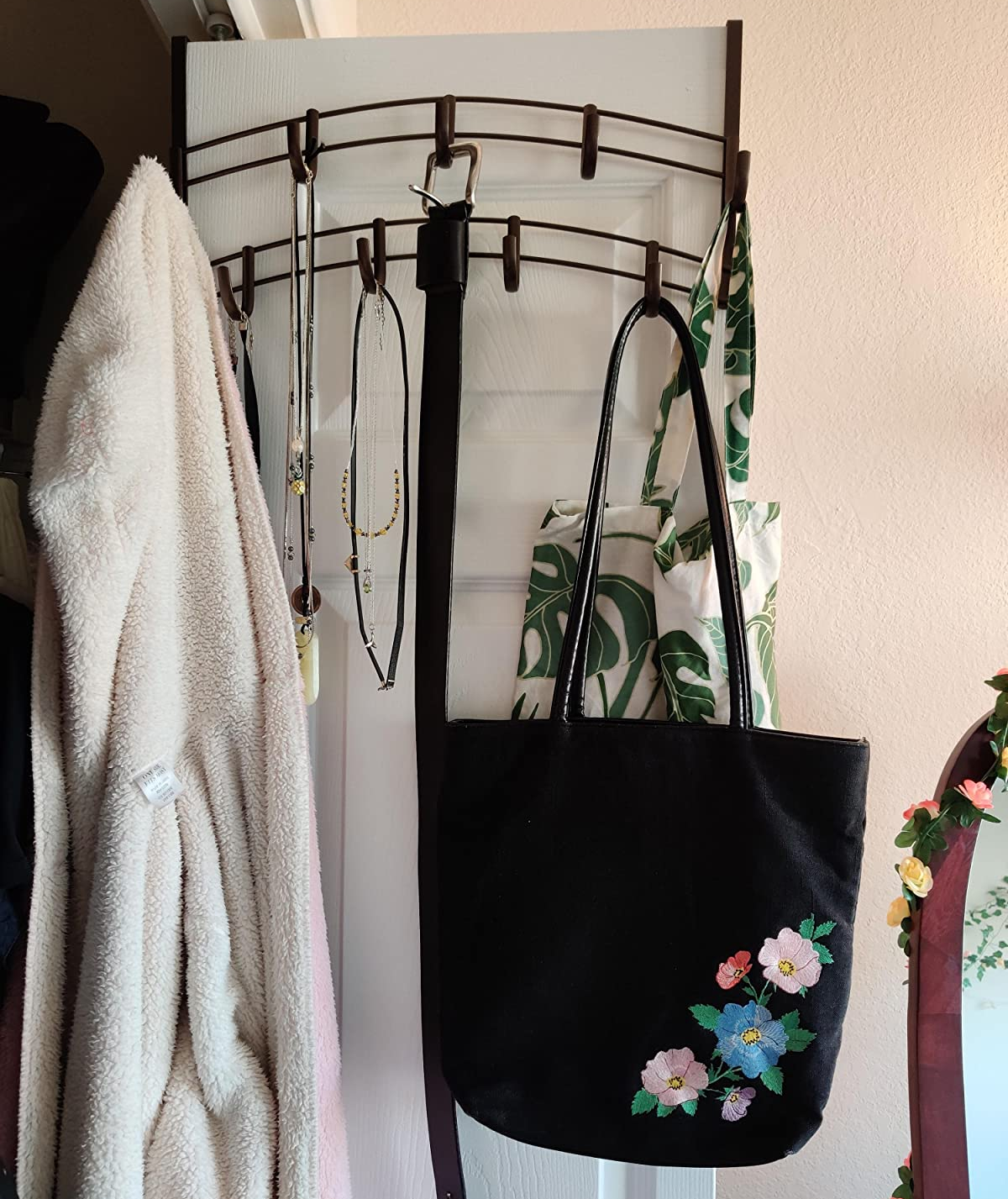 Reviewer photo of the rack over a door holding a purse, jacket, and necklaces