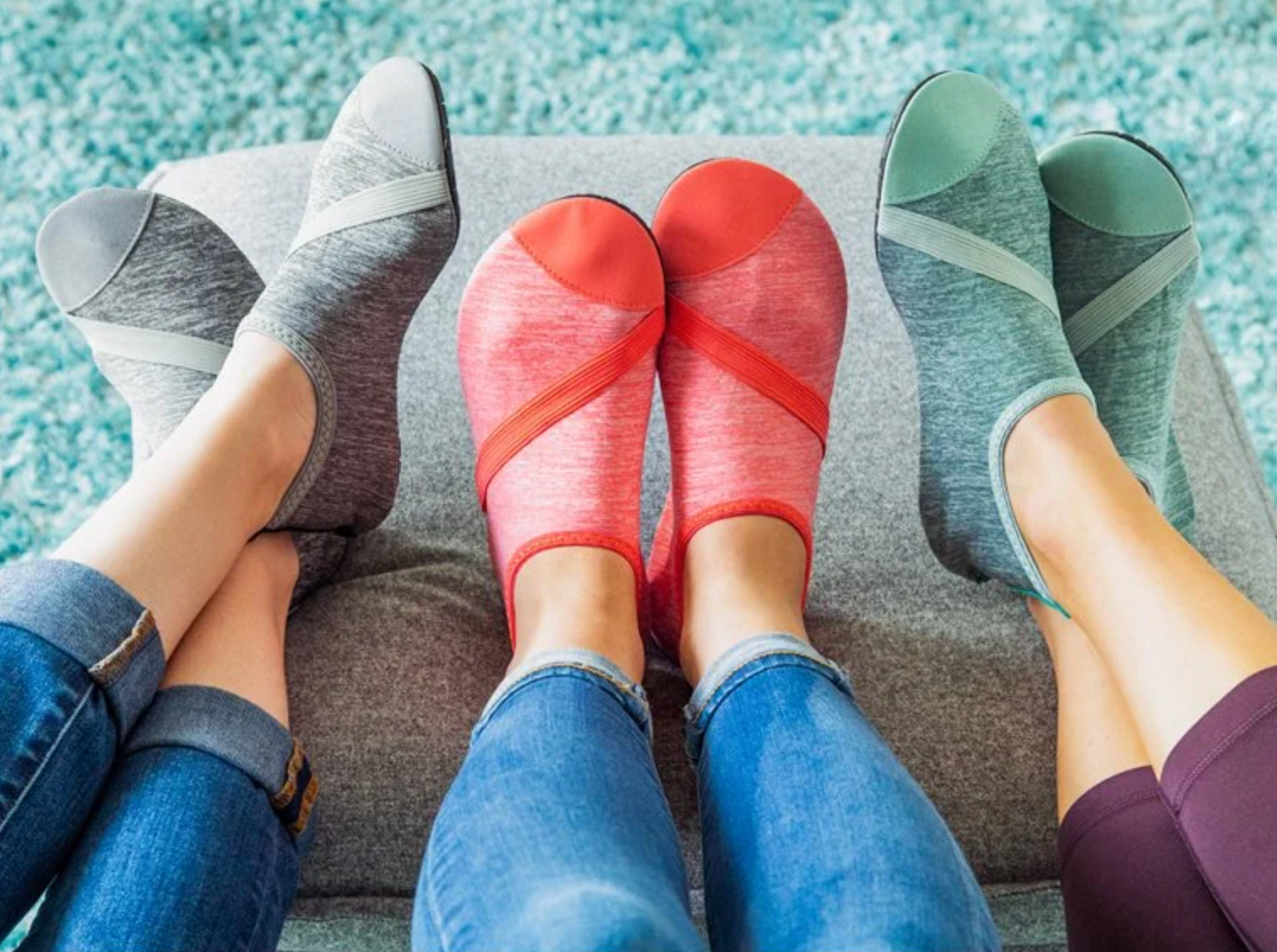Models wearing sock-like shoes in heathered gray, coral, and mint green colors
