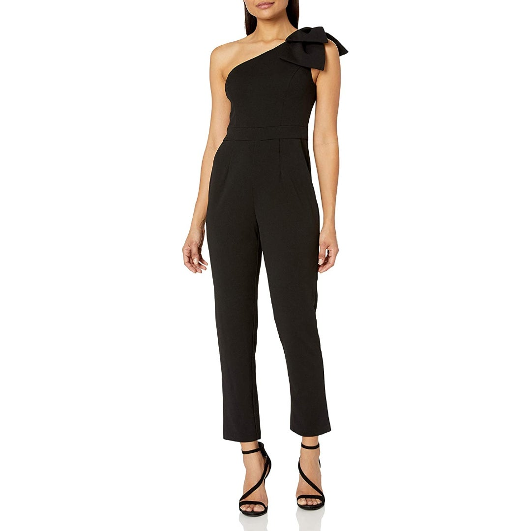 a model in a black one-shouldered jumpsuit with a bow on the shoulder